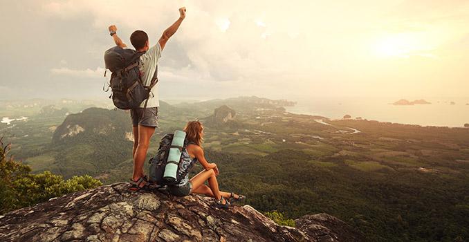Zwei Backpacker mit Rucksack auf einer Klippe
